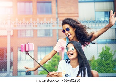 Two exuberant female friends making exaggerated gestures while taking a self portrait outside with pink cell phone attached to stick pole