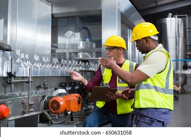 Two factory workers discussing while monitoring drinks production line at factory