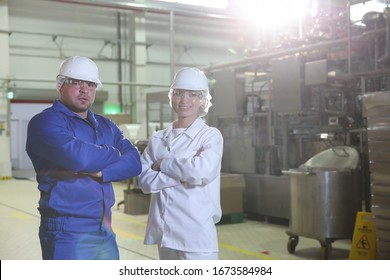 two factory workers on the background of the equipment line at the factory. the factory engineers look at camera
