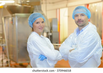 Two factory workers stood with their arms folded