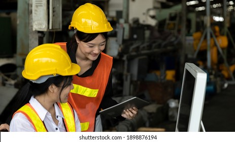 Two factory workers or technicians are using computer and technology to check stock in a heavy machinery warehouse