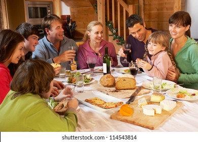 Two Familes Enjoying Meal In Alpine Chalet Together