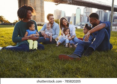 Two families with daughters sitting on lawn