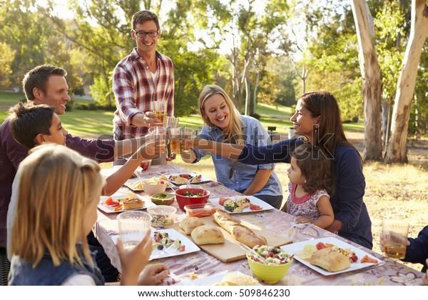 Zwei Familien, die am Picknick am Tisch im Park Toast machen