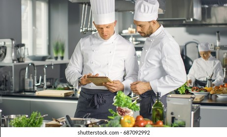 Two Famous Chefs Exchange Ideas About Video Blog Recipe they Watching on Tablet. They are Working in Big Restaurant Kitchen.