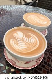 Two fancy lattes with fern pattern