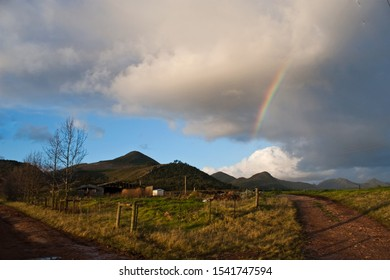 Two farm roads converge and in the background, there is a rainbow in the clouds.