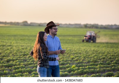 Two farmers man and woman with tablet standing in soybean field in front of tractor at sunset