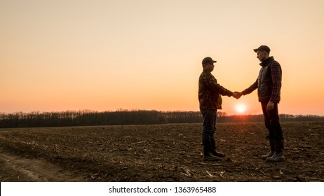 Two farmers on the field shake hands at sunset. Wide lens shot
