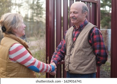 Two farmers senior woman and man shaking hands and takling to each other on sunny day