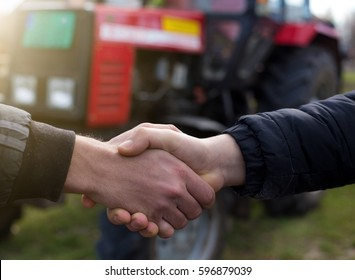 Two farmers shaking hands in front of tractor in field
