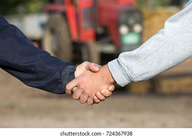 Two farmers shaking hands in front of tractor on farm. Agribusiness concept