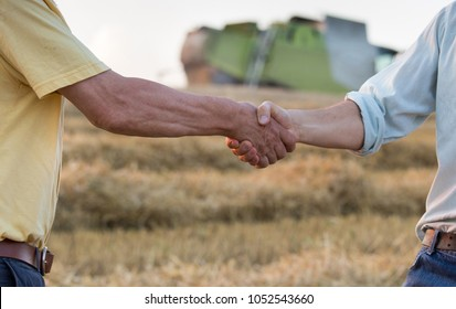 Two farmers shaking hands on wheat field during harvest. Combine harvester working in background