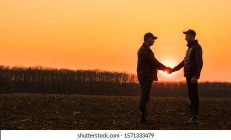 Two farmers shaking hands on a plowed field