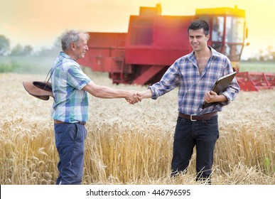 Two farmers shaking hands on wheat field while combine harvesting behind
