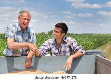 Two farmers shaking hands over trailer full of grains. Agriculture and farming concept