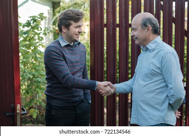 two farmers shaking hands and talking to each other on sunny day