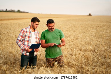 Two farmers stand in wheat stubble field, discuss harvest, crops. Senior agronomist with touch tablet pc teaches young coworker. Innovative tech. Precision farming with online data management soft. - Shutterstock ID 1797615382