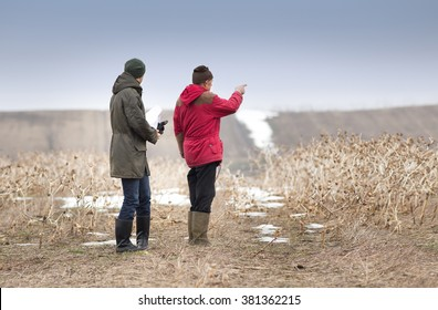 Two farmers standing on field in winter time