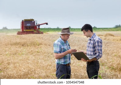 Two farmers standing on wheat field at harvest with combine harvester working in background
