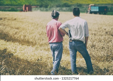 Two farmers standing on wheat field at harvest