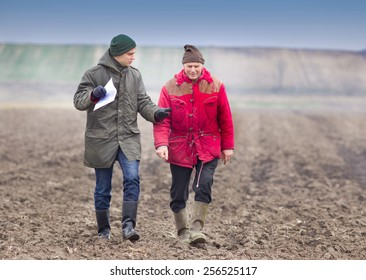 Two farmers walking on plowed field in winter time