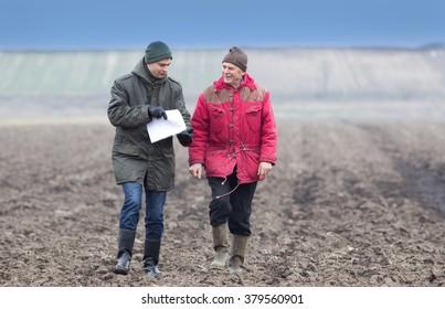 Two farmers walking on plowed field in winter time