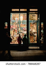 Two fascinated children in front of a toy store with balloons at night in prague in winter at christmas