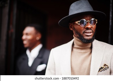 Two fashion black men. Fashionable portrait of african american male models. Wear suit, coat and hat.