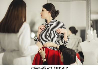 Two fashion designers adjusting red skirt on model in the studio