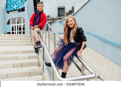 Two fashion kids: Beautiful Children play on the railing in the street on the stairs. Lovely boy and long-haired girl model happy in the city. Have fun. Slide and ride on the railing.