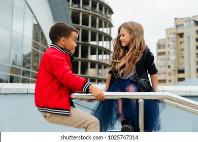 Two fashion kids: Beautiful Children play on the railing in the street on the stairs. Lovely boy and long-haired girl model happy in the city. red black jackets, blue skirt.