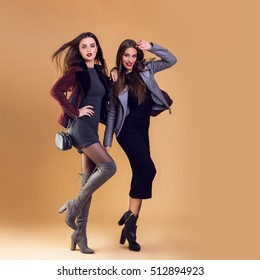 Two fashion models in winter or autumn  clothes posing in studio on beige background. Elegant casual jacket, high heels. Full length image.