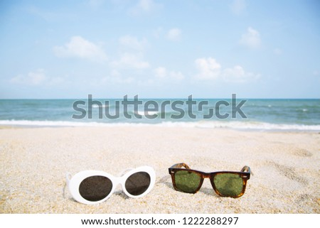 2bab57e525f0 two fashion sunglasses close up on the beach sand in summer. Beautiful sea  view clear