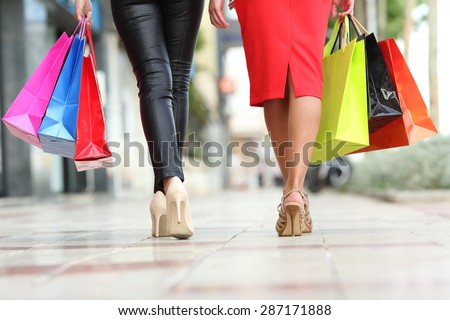 Two fashion women legs walking with colorful shopping bags in the street of a city