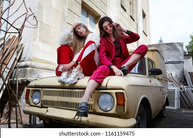 Two fashion young girl siting on the backyard. Stylish woman in a red suit and sunglasses and in white fur and sport red pants .Emotioanl shot.Motion.