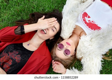 Two fashion young happy girl laying on green grass .Laughing and show tongue the other in pink sunglases.Stylish woman in red jacket and other in white fur and t-shirt.Pink sunglasses.