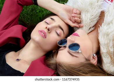 Two fashion young happy girl laying on green grass .Close eyes and other in blue sunglases.Stylish woman in red jacket and other in white fur and t-shirt.Blue sunglasses. .Fashion