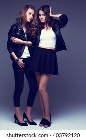 Two fashion young women posing in studio. Leather jackets, skirt, jeans, heels