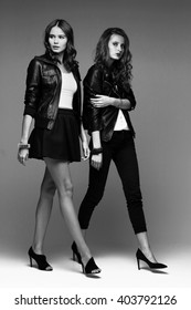 Two fashion young women posing in studio. Leather jackets, skirt, jeans, heels. Black and white image.