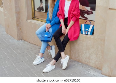 Two fashion young women wearing knit cardigans,sneakers and jeans with pythone handbags in hand .