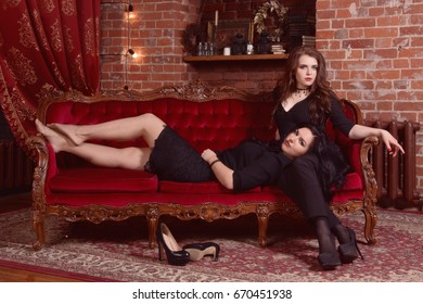 Two fashionable beautiful women in a black at vintage interior.