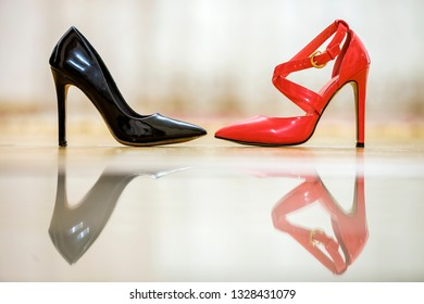 Two fashionable comfortable high heel leather female shoes, red and black, isolated on light copy space background. Style and fashion, modern footwear concept.