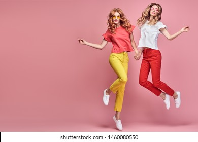 Two fashionable girl jump Smiling in colorful outfit on pink. Beautiful easy-going woman in red yellow pants, Stylish curly hair having fun. Joyful funny slim sisters friends, happy fashion concept