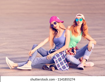 Two fashionable Skaters best friend Laughing and fun. Outdoor Urban. Playful happy Girl with peace sign. Young Beautiful Model Woman in Fashion Trendy Outfit, Sunglasses