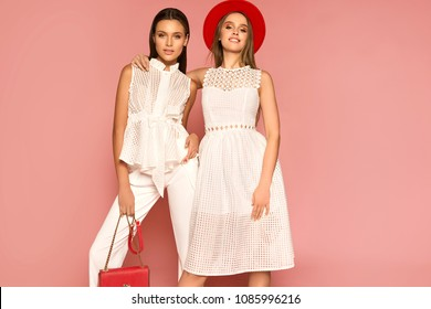 Two fashionable women in nice clothes posing over pink background. Fashion spring summer photo.