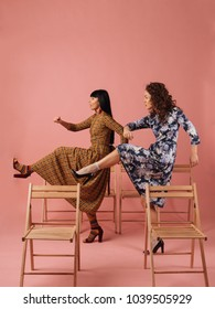 Two fashionable women in nice dresses having fun. Fashion photoshoot on pink background.