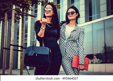 Two fashionable women in stylish clothes and sunglasses posing in a middle of business urban district.