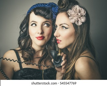 Two fashionable young female friends in vintage clothes sharing retro telephone