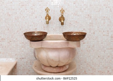Two faucets and two copper bowl in turkish bath